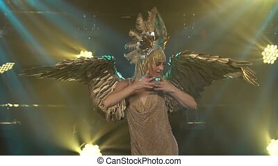 The Greek goddess Artemis with golden wings and a chic headdress sings and dances on stage. Young woman presents a theatrical vocal dance show. Close up