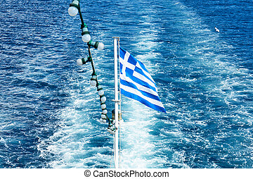The Greek national flag flying from the stern of a ferry boat