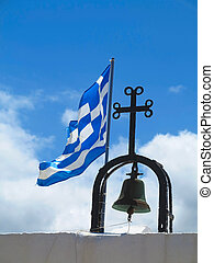 The Greek National flag near cross of small church against blue cloudy sky