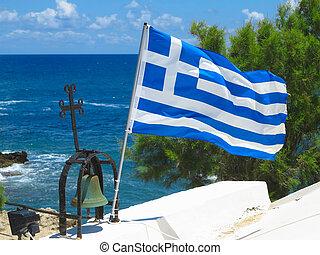 The Greek National flag near cross of small church against blue cloudy sky
