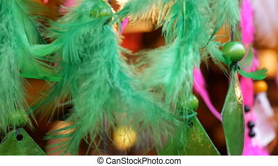 The green feathers of a dreamcatcher who sway in wind - The...