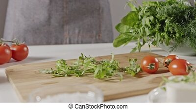 The green leaves of the arugula fall onto cutting wooden...