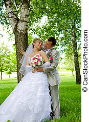 The groom and the bride in park near a tree