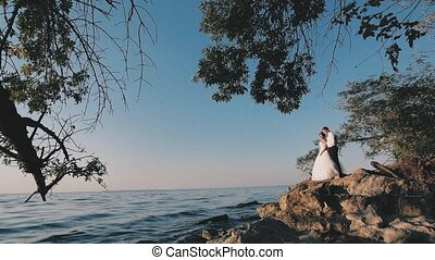 the groom and the bride on the shore