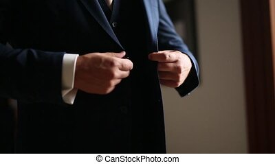 The groom buttons up the jacket. Groom wedding dress