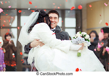 The groom carrying bride in his arms, the crowd throws petals and rice. Happy wedding.