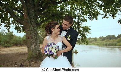 The groom embraces the bride, and they stand by the river