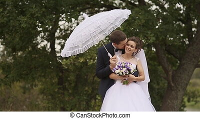 The groom embraces the bride under white umbrella