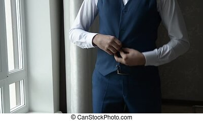 the groom fastens the vest