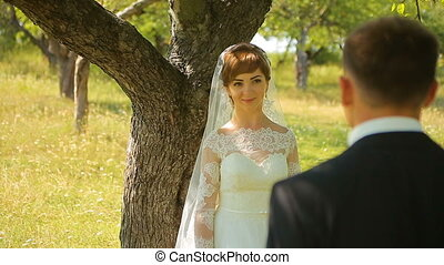 The groom gives the bride a bouquet of her standing on one knee on nature