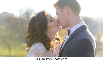 the groom kisses the bride in a park at sunset the sun shot in slow motion  close up
