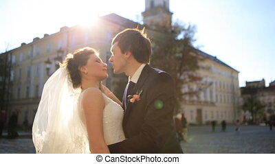 The groom kisses the bride in city shot in slow motion  close up