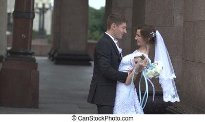 The groom kisses the bride near pillars