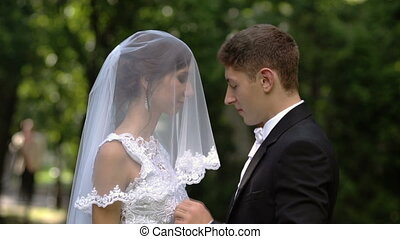 The groom lifts the veil from the bride's face and kisses her