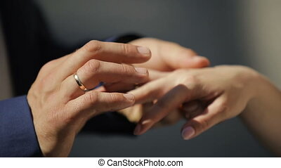 The groom puts the wedding ring on finger of the bride. Close up