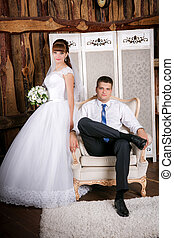 The groom sits in a chair and the  bride stands near groom in the room with a beautiful interior