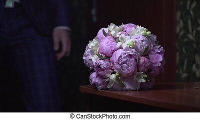 The groom takes the bridal bouquet