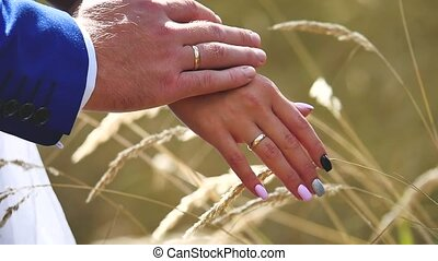 the groom touches the tender hand of the bride. wedding...