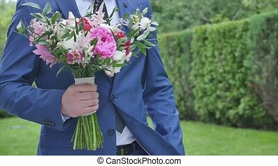 the groom walk with a bouquet