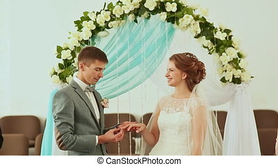 The groom wears a wedding ring to the bride.