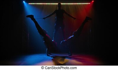 The group of acrobat gymnast men on balance pose. A difficult acrobatic stunt performed in a studio with neon light. Slow motion