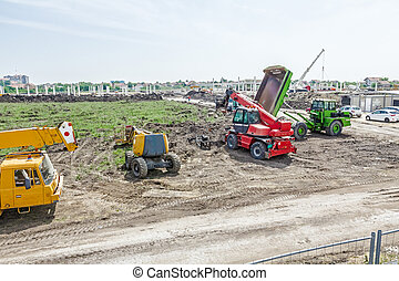 The group of construction machinery is parked at building site