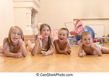 The group of four children lying on the floor. Four happy children lie on the floor. Happy large family