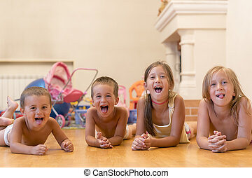 The group of four children lying on the floor. Four happy children lie on the floor.