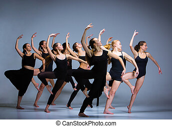 The group of modern ballet dancers dancing on gray...