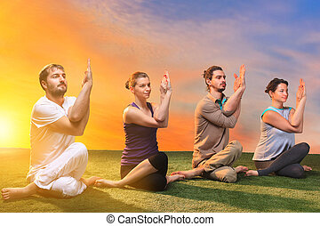 The group of people doing yoga exercises