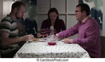 The group of people having dinner at the table