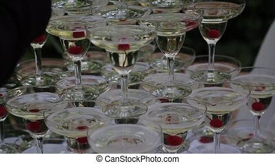 The guests' hands take glasses with bubbling wine at the party. Glasses are built in the pyramids. No recognizable persons.