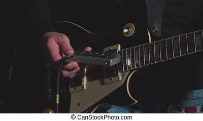 The guitar player adjusts the guitar using a tunerSoft focus