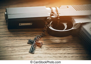 The gun with a rosary with black beads