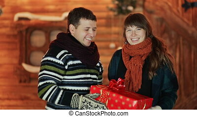 The guy and the girl give the viewer a red Christmas present on the background of a fairy-tale house. Christmas and New Year theme.