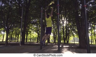 The guy does chin-ups on a horizontal bar
