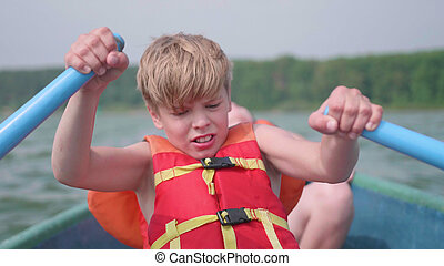 The guy floats on the boat. Teen independently operates a boat with the help of oars. Extreme sport