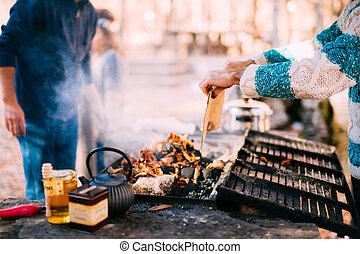 The guy fries a shish kebab on an open fire
