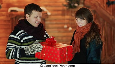 The guy gives his girlfriend a red Christmas present against the backdrop of a fairy-tale house. The girl is very happy. Christmas and New Year theme.