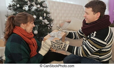 The guy gives the girl Christmas gifts. The girl model shows off a gift to the viewer and also shows the sign of the like - thumb up.. Cozy homely atmosphere.