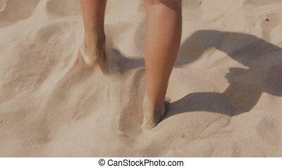guy goes through the hot beach sand - The guy goes through...