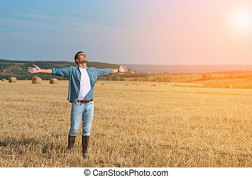 The guy in jeans, shirt, rubber boots in the field with his hands open, the concept of freedom, motivation, movement, a copy of space