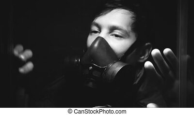 The guy in the gas mask breathes heavily in a dark transparent room