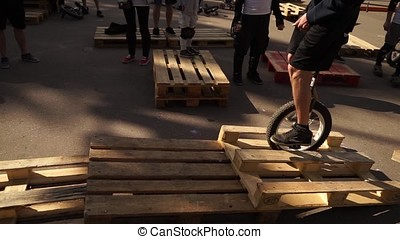 The guy is engaged in a trilateral on a unicycle for pallets-2