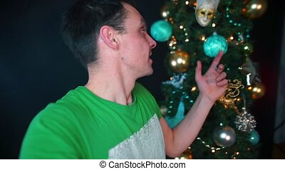 The guy is recording video from his hands near the Christmas tree.
