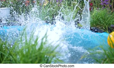 The guy is swimming in a small lake on a hot summer day. The boy jumps into the water, creates splashes of water. Garden, flowers and plants around the lake. Happy childhood