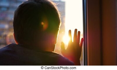 the guy looks out the window at the sun. Plays a hand with sunlight