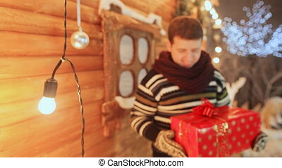 The guy on the background of a wooden fairy house gives a gift to the viewer. Christmas and New Year theme.