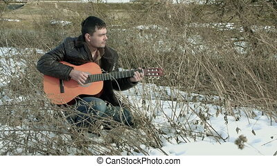 The guy playing the guitar in nature