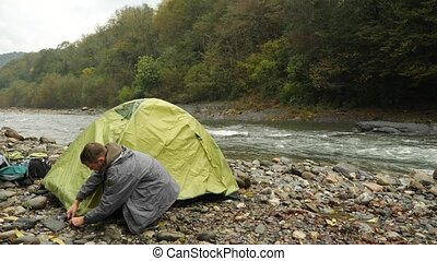 The guy puts a tourist tent on the bank of a mountain river....
